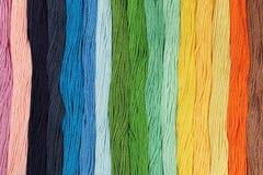 Des fils multicolores de coton pour la broderie sont arrangés dans une rangée Photographie stock