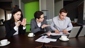 Des financiers, deux hommes et la femme sont chargés avec le gadge de travail et d'utilisation image stock