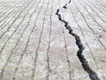 Des fissures, crevasses, dalles en béton ceci est provoquées par la construction non standard images stock