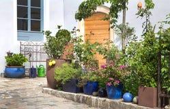 Des fleurs dans des pots de terre cuite - faites du jardinage devant une maison Photo libre de droits