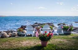 Des fleurs mises en pot patriotiques sont vues parmi les chaises blanches d'adirondack donnant sur la belle baie bleue Photographie stock libre de droits