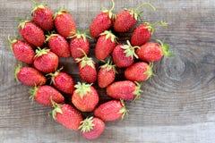 Des fraises fraîches sont présentées dans en forme de coeur d'isolement sur le fond en bois Images libres de droits