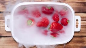 Des fraises juteuses mûres dans un plat blanc sont couvertes de brouillard de matin clips vidéos