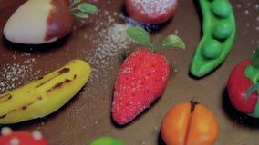 Des fruits de massepain sont placés sur un conseil brun en bois sur une table clips vidéos