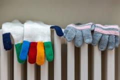 Des gants tricotés sont séchés sur un radiateur blanc photographie stock libre de droits