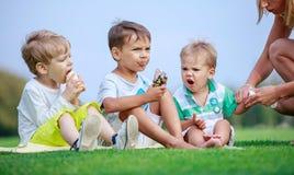 Des garçons plus âgés mangeant la crème glacée, jeune femme essuyant des mains du plus jeune fils Photographie stock libre de droits
