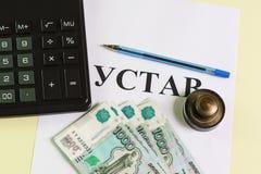 Des Geschäfts Leben noch Taschenrechner, Stempel, Stift und russisches Geld auf dem Tisch Stockbild