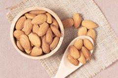 Des graines d'amande dans une tasse et une cuillère sont placées sur un sac et un W tissés image libre de droits
