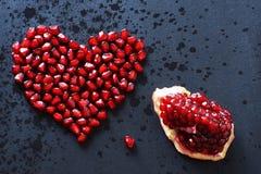 Des graines de grenade sont empilées sous forme de coeur sur un fond noir, arrosé avec de l'eau, à côté d'un quart d'un pomegrana Image libre de droits