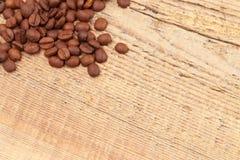 Des grains de café au-dessus de vieille table en bois - fermez-vous vers le haut du tir images stock