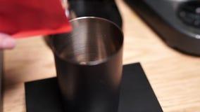 Des grains de café rôtis sont versés vers le bas dans la tasse en métal dans un café banque de vidéos