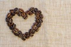 Des grains de café sont présentés sous forme de coeur sur un napk beige Images stock