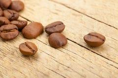 Des grains de café sur la vieille table en bois - fermez-vous vers le haut du tir de studio image libre de droits