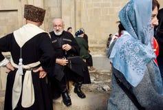 Des hommes plus âgés dans des costumes nationaux parlant dans la foule des personnes pendant la célébration du jour de ville Images stock