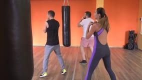 Des hommes s'exerçants et une fille sont formés dans le gymnase par des arts martiaux, car, boîte clips vidéos
