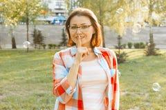 Des im Freien erwachsene Frau Porträts zeigt Zeichen ruhig, Geheimnis, Grifffinger nahe ihren Lippen Hintergrundstadtpark bei Son lizenzfreies stockfoto