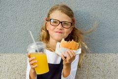 Des im Freien glückliches kleines Schulmädchen Porträts mit dem Mittagessen Stockfoto