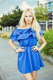 Des im Freien lächelndes Lebensstilporträt Sommers der recht jungen Frau Lange blonde Haare, blaue Ausstattung im Park Blaues Kle Stockbilder