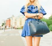 Des im Freien lächelndes Lebensstilporträt Sommers der recht jungen Frau mit großer blauer Handtasche Lange blonde Haare, blaue A Lizenzfreie Stockfotos