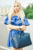 Des im Freien lächelndes Lebensstilporträt Sommers der recht jungen Frau mit großer blauer Handtasche und hallo Fersenschuhe Lang Stockfotografie