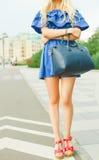 Des im Freien lächelndes Lebensstilporträt Sommers der recht jungen Frau mit großer blauer Handtasche und hallo Fersenschuhe Lang Stockfoto