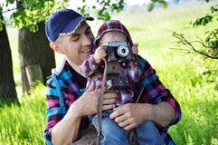 Des im Freien lächelndes Lebensstilporträt Sommers des glücklichen Vaters und kleinen des Babys, die Spaß mit Retro- Kamerareisef Lizenzfreies Stockbild