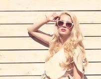 Des im Freien schöne junge blonde Frau sinnlichen Mode-Porträts des Sommers ein weißes Kleid, das auf dem Hintergrund von hölzern Lizenzfreie Stockbilder