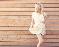 Des im Freien schöne junge blonde Frau sinnlichen Mode-Porträts des Sommers hebt den Rand eines weißen Kleides an, das auf dem Hi Lizenzfreie Stockfotografie