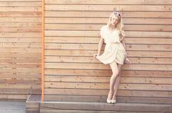 Des im Freien schöne junge blonde Frau sinnlichen Mode-Porträts des Sommers hebt den Rand eines weißen Kleides an, das auf dem Hi Stockfoto