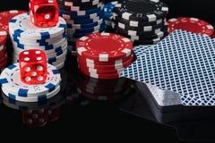 Des jetons de poker et les cartes sur un fond noir sont reflétés Image stock
