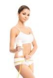 Des jeunes et une femme d'ajustement mesurant ses hanches avec une bande Image stock