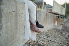 Des jeunes mariés s'asseyent sur un mur de roche par la plage Photos stock
