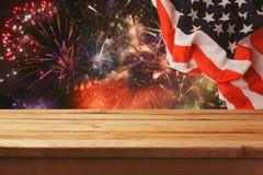 des Juli-Hintergrundes Holztisch über Feuerwerken und USA-Flagge Straßen-Clown grüßt Leute Stockfotografie