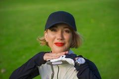 Des Lebensstils Porträt draußen der jungen schönen und glücklichen Frau am Spielen des lehnenden Bonbons des Golfs auf dem Verein stockfotografie