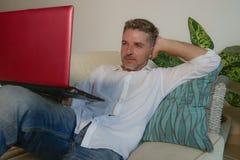 Des Lebensstils Porträt zuhause des jungen glücklichen und attraktiven Geschäftsmannes, der mit Laptop-Computer vom Haus bequem a lizenzfreies stockbild