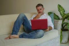 Des Lebensstils Porträt zuhause des jungen glücklichen und attraktiven Geschäftsmannes, der mit Laptop-Computer vom Haus bequem a stockfotografie