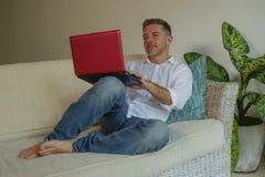 Des Lebensstils Porträt zuhause des jungen glücklichen und attraktiven Geschäftsmannes, der mit Laptop-Computer vom Haus bequem a lizenzfreies stockfoto
