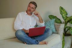 Des Lebensstils Porträt zuhause des jungen glücklichen und attraktiven Geschäftsmannes, der mit Laptop-Computer vom Haus bequem a stockbild