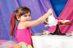 Des Mädchens der Tee-und des kleinen Kuchens Partei lizenzfreie stockbilder