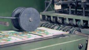 Des magazines imprimées sont libérées une bande de conveyeur et puis en obtenant sous une presse de roulement banque de vidéos