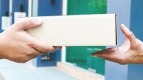 Des mains aux mains Plan rapproché des mains tenant la boîte en carton à la maison photo stock