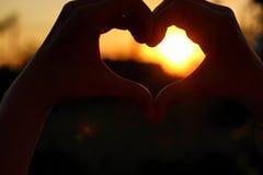 Des mains de femmes sont croisées sous forme de coeur par lequel les rayons du soleil font la manière au coucher du soleil Photos stock