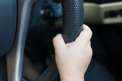 des mains de plan rapproché du conducteur d'enfants sont rattrapées en vigueur Photo stock