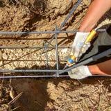 Des mains de travailleurs utilisant le fil d'acier et la pince pour fixer le rebar avant béton est versées au-dessus de lui photos stock
