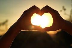 Des mains du ` s de femmes sont croisées sous forme de coeur par lequel les rayons de ` du soleil font la manière au coucher du s Photos stock