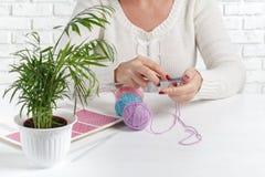 Des mains du ` s de femmes sont tricotées Processus du tricotage Beau tricotage en bois sensible avec des aiguilles de tricotage Image libre de droits