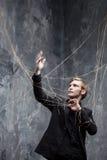 Des mains sont attachées Le jeune homme dans le costume noir obtenu s'est propagé le Web Concept de manipulation et d'esclavage Image libre de droits