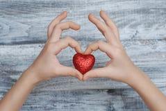 Des mains tenant le coeur, les relations et le concept rouges d'AMOUR - fermez-vous de la main montrant le coeur rouge sur le fon Photographie stock