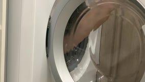 Des Mannes pflücken herauf Kleidungswaschmaschine mit der Hand Saubere und gesunde Konzepte stock footage