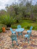 Des meubles métalliques de jardin sur une terrasse de tuile d'argile photos stock